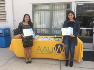 Picture of two girls in front of an AAUW table.